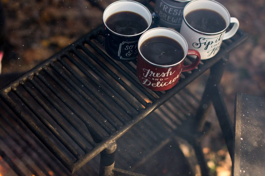 four mugs of coffee on a campfire grate